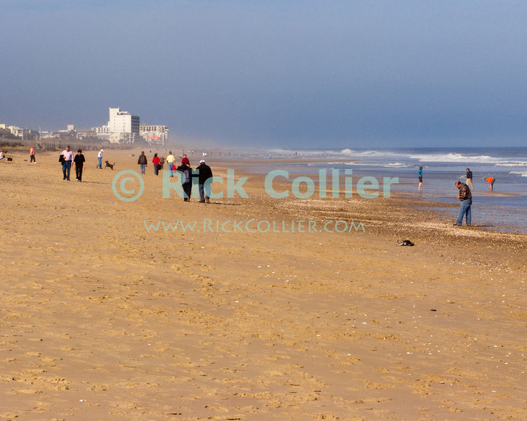 Walkers and beachcombers emerge to explore the widened beach as the sun finally emerges after a nor'easter clears out from Bethany Beach, Delaware, USA.