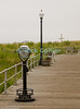 """Symbols"" - Icons of modern American life at the beach adorn the boardwalk at Ocean Grove, New Jersey, USA:  A pay viewer, streetlight, bench, and a cross.<br /> <br /> <br /> USA ""New Jersey"" NJ ""Ocean Grove"" Ocean Grove Christian dune beach boardwalk pay viewer binoculars light streetlight bench seat cross"