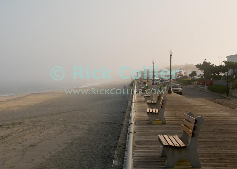 """Foggy Boardwalk"" - Fog begins to lift from a nearly deserted boardwalk and beach at sunset.  Allenhurst, New Jersey, USA.<br /> <br /> <br /> USA ""New Jersey"" NJ Allenhurst boardwalk bench benches streetlight railing streetlight beach sand Atlantic Ocean fog mist haze sunset"