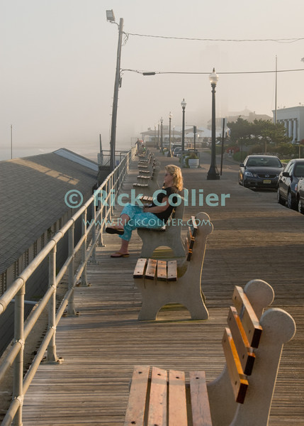 """Waiting"" - A woman waits in the sunset.  The boardwalk, Allenhurst, New Jersey, USA.<br /> <br /> <br /> USA ""New Jersey"" NJ Allenhurst boardwalk bench benches streetlight railing woman waiting patience"