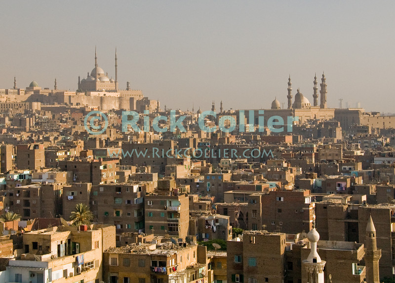Skyline -- Cairo, Egypt.  The Citadel of Salal ad-Din (Saladin) and the towering Mosque of Sultan Hassan dominate the Cairo skyline.  Viewed from the minaret at the Bab Zwayla gate to old walled Cairo. © Rick Collier<br /> <br /> <br /> <br /> <br /> <br /> <br /> Egypt Egyptian Cairo tourist tourism history historic antiquities Islamic old street shop window building city wall arch 'city gate' Zwayla 'Bab Zwayla' minaret dome mosque skyline cityscape 'old town' 'walled city' Citadel Saladin Hassan