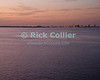 The lights of Tampa and St. Petersburg, Florida, begin to take the place of sunlight at the shore, as an orange dusk falls over Tampa Bay, Florida.  Taken from the deck of the Carnival Legend cruise ship.  © Rick Collier