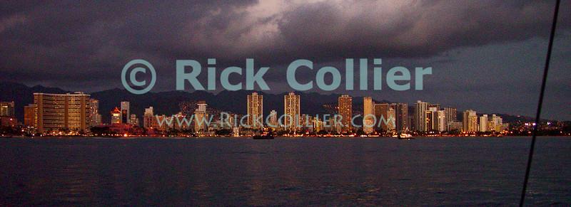 Tall buildings lining Waikiki beach begin to light up at dusk.  Waikiki, Honolulu, Oahu, Hawaii.  © Rick Collier<br /> <br /> <br /> <br /> <br /> <br /> <br /> <br /> Hawaii Hawai'i Oahu Honolulu Waikiki dusk dark evening light lights sea ocean apartment building condomunium condo hotel hotels beach skyline panorama