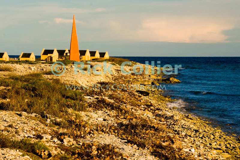 """Bonaire, Netherland Antilles -- Slave huts surround the orange marker that told sailing captains they had arrived at the anchorage for one of the several salt stations in the south of Bonaire (Orange Pan).    © Rick Collier<br /> <br /> <br /> <br /> <br /> Bonaire; """"Netherlands Antilles""""; Caribbean; tropic; tropical; vacation; destination; salt; anchorage; """"salt pan""""; slave; """"slave hut""""; """"slave quarters""""; house; marker; orange; """"Orange Pan""""; """"Orangepan""""; seashore; ocean; sea; view;"""
