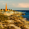 "Bonaire, Netherland Antilles -- Slave huts surround the orange marker that told sailing captains they had arrived at the anchorage for one of the several salt stations in the south of Bonaire (Orange Pan).    © Rick Collier<br /> <br /> <br /> <br /> <br /> Bonaire; ""Netherlands Antilles""; Caribbean; tropic; tropical; vacation; destination; salt; anchorage; ""salt pan""; slave; ""slave hut""; ""slave quarters""; house; marker; orange; ""Orange Pan""; ""Orangepan""; seashore; ocean; sea; view;"
