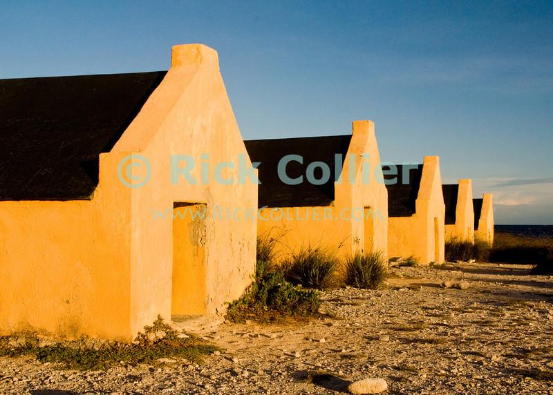 "Bonaire, Netherland Antilles -- Slave huts at one of the several salt stations in the south of Bonaire (Orange Pan).   © Rick Collier<br /> <br /> <br /> <br /> <br /> Bonaire; ""Netherlands Antilles""; Caribbean; tropic; tropical; vacation; destination; salt; anchorage; ""salt pan""; slave; ""slave hut""; ""slave quarters""; house; marker; orange; ""Orange Pan""; ""Orangepan""; seashore; ocean; sea; view;"