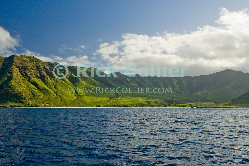 The island of Oahu looks like a primeval wilderness when viewed from the sea.<br /> <br /> <br /> <br /> <br /> Hawaii Oahu beach island rain forest cloud sea shore seashore beach sunlight