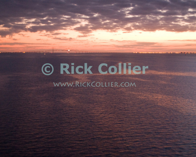 The sunshine skyway bridge appears at the mouth of the Tampa bay, Florida -- silhouetted in the orange sunset and framed by reflections of the sunset from clouds and sea.  Taken from the deck of the Carnival Legend cruise ship.  © Rick Collier