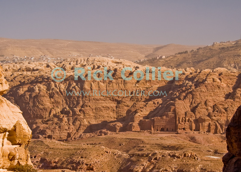"""""""Old and New"""" -- The new town of Wadi Musa occupies the hills outside the Petra valley, where the Nabateans carved their tombs into the rock walls.  © Rick Collier<br /> <br /> <br /> <br /> Jordan Petra Nabatea Nabatean Rome Roman ruin archeology 'ancient world' antiquity cave 'cave dwelling' antiquities Bible Biblical civilization history historic desert stone cliff wall carve carved facade tourist tourism archeology tomb tombs valley desert necropolis town village arab landscape 'Wadi Musa'"""