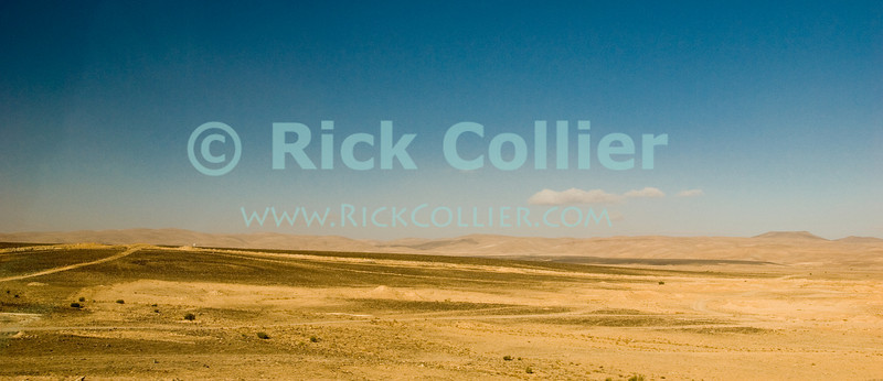 """Desert"" -- The high desert south of Amman, Jordan is peppered in places with dark volcanic rock.  © Rick Collier<br /> <br /> <br /> <br /> Jordan car van arab bedouin highway 'desert highway' desert"