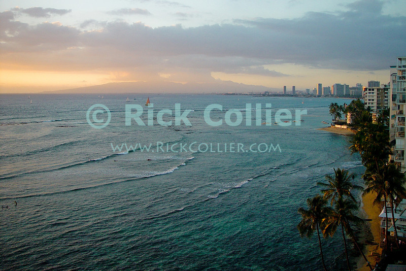 Warm evening sunlight illuminates boats in the bay at Waikiki, Honolulu, Oahu, Hawaii.  © Rick Collier<br /> <br /> <br /> <br /> <br /> <br /> <br /> <br /> Hawaii Hawai'i Oahu Honolulu Waikiki beach bay sail boats sailboat sailboats city skyline seashore evening