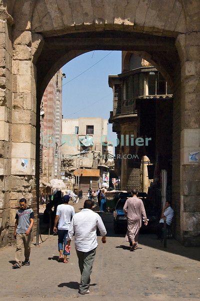 """Cairo, Egypt -- Bab Zuwayla gate.  One of the three first gates installed around the historic walled city of Cairo, standing at the southern boundary of old Fatimid Cairo.  The two minarets atop this tower actually belong to the nearby Mosque of al-Mu'ayyad, which sits just inside this gate (on the left).  For a small fee, it is possible to climb the minarets for a spectacular view of old and new Cairo. © Rick Collier / RickCollier.com.<br /> <br /> <br /> <br /> <br /> <br /> travel; vacation; tour; tourism; tourist; destination; Egypt; Cairo; city; view; gate; walls; bab; """"Bab Zuwayla""""; Zuwayla; minaret; Fatimid; Fatmid; """"city gate""""; """"Islamic Cairo"""";"""