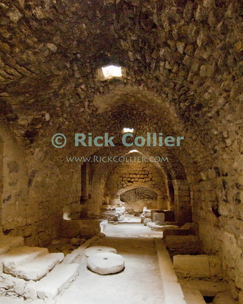The kitchen chamber at Karak Castle, with the original fireplace and cistern at the end and two grinding wheels on the floor.  The Crusader castle at Karak guarded the eastern border of the Kingdom of Jerusalem after the first Crusade. © Rick Collier<br /> <br /> <br /> <br /> <br /> Jordan Karak al-Karak castle crusader crusades knights fort fortress history historic tourist tourism antiquities 'Kingdom of Jerusalem' interior stables tunnel chamber windows sunlight kitchen skylights stone
