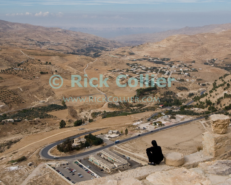 Overlook.  A young man perches right on the edge of Karak Castle's battlements, atop a sheer face several hundred feet above the Wadi al-Karak, below.  The bluffs on the Israeli side of the Dead Sea are clearly visible in the distance.  According to legend, the ancient Biblical condemned cities of Sodom and Gomorrah were between Karak and the Dead Sea, in this view.  The Crusader castle at Karak guarded the eastern border of the Kingdom of Jerusalem after the first Crusade. © Rick Collier<br /> <br /> <br /> <br /> <br /> Jordan Karak al-Karak castle crusader crusades knights fort fortress history historic tourist tourism antiquities 'Kingdom of Jerusalem' battlement battlements walls keep chapel ruin ruins view panorama cross-country arab