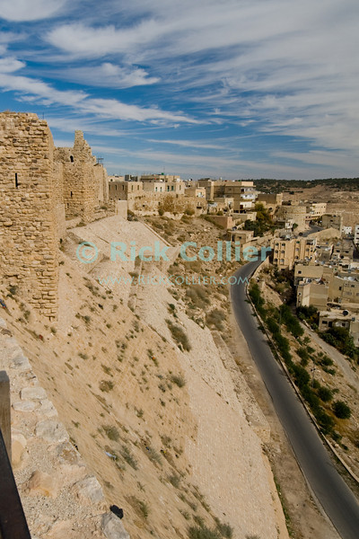 Looking past the towers and glacis of Karak Castle, one can see the town of Karak beyond.  The Glacis was a particular finished face leading to the battlements, built to be too steep to climb and so making the Castle nearly impregnible from this side.  Karak's glacis was the scene of particular cruelty by the last crusader lord, which led directly to the castle being conquered by Saladin.  The Crusader castle at Karak guarded the eastern border of the Kingdom of Jerusalem after the first Crusade. © Rick Collier<br /> <br /> <br /> <br /> <br /> Jordan Karak al-Karak castle crusader crusades knights fort fortress history historic tourist tourism antiquities 'Kingdom of Jerusalem' battlement battlements walls glacis valley wadi town arab village road