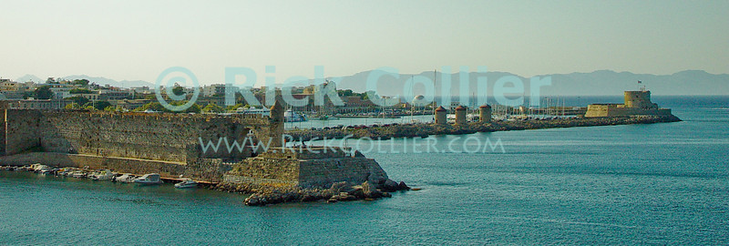 Rhodes Town, on the island of Rhodes, Greece.  Famed as the legendary site of the Colossus of Rhodes, the ancient harbor is walled, with armories (the turret-like stuctures) and a fort standing on the outer jetty.  © Rick Collier<br /> <br /> <br /> <br /> <br /> <br /> Greece Rhodes tour tourism tourist tourists citadel fort fortress castle crusader crusaders knight knights templar templars wall walls armory fort fortress jetty jetties harbor marina boat boats sailboats