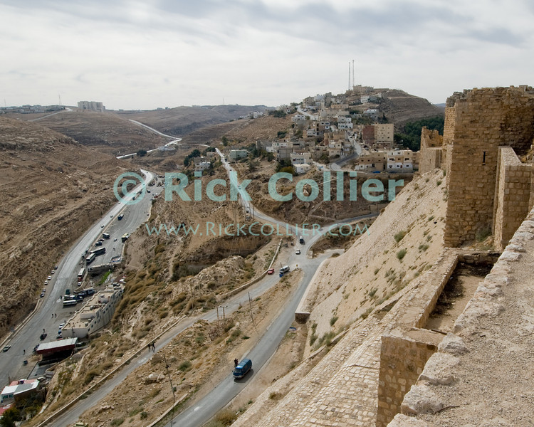 The Glacis of Karak Castle overlooks the main roads leading into the town.  The Glacis was a particular finished face leading to the battlements, built to be too steep to climb and so making the Castle nearly impregnible from this side.  Karak's glacis was the scene of particular cruelty by the last crusader lord, which led directly to the castle being conquered by Saladin.  The Crusader castle at Karak guarded the eastern border of the Kingdom of Jerusalem after the first Crusade. © Rick Collier<br /> <br /> <br /> <br /> <br /> Jordan Karak al-Karak castle crusader crusades knights fort fortress history historic tourist tourism antiquities 'Kingdom of Jerusalem' battlement battlements walls glacis arab town village road highway