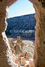 Bandelier National Monument, near Los Alamos and Santa Fe, New Mexico, USA.  A cave entrance frames the view of Frijoles Canyon, showing the remains of an ancient pueblo below. © Rick Collier<br /> <br /> <br /> <br /> <br /> <br /> <br /> US USA New Mexico Santa Fe Bandelier National Monument Frijoles Canyon cliff cliffs valley canyon native american cave dwelling pueblo view tree trees forest woods stream river