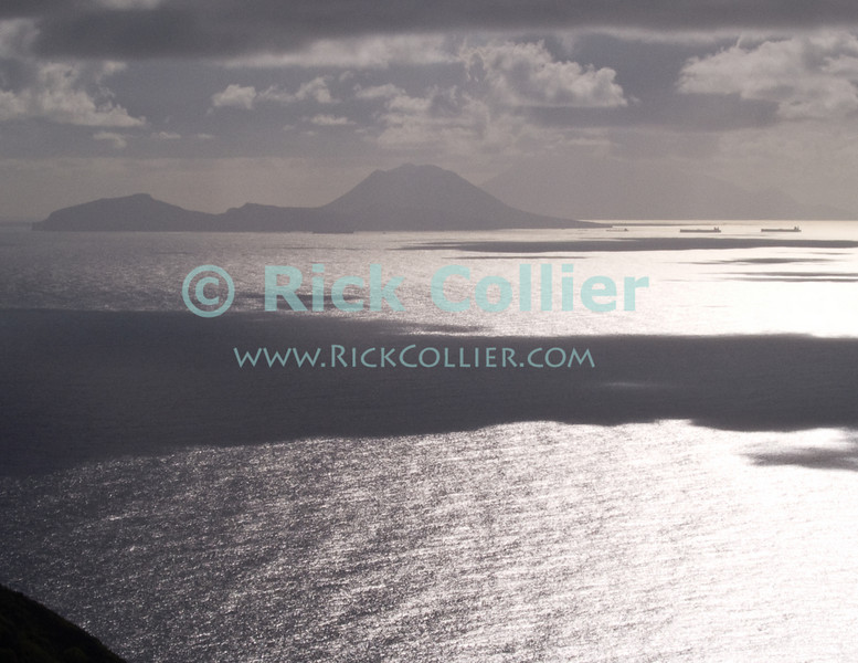 Saba - A scenic view - St. Eustatius is silhouetted by the early morning Caribbean sun on Saba.  St. Kitts is visible in the distance beyond St. Eustatius.  © Rick Collier