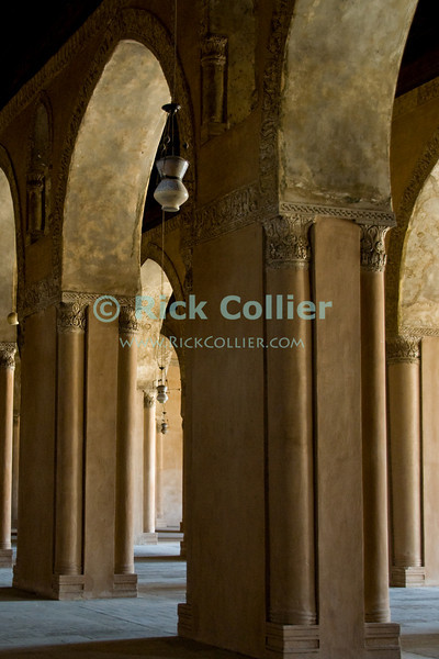 """Cairo, Egypt -- Bright light shines through lovely arched openings into the arcades surrounding the central plaza and fountain at the historic ibn Tulun mosque.   © Rick Collier / RickCollier.com<br /> <br /> <br /> <br /> travel; vacation; tour; tourism; tourist; destination; Egypt; Cairo; mosque; madrassa; Tulun; """"ibn Tulun""""; arcade; arch; arches; archways; passage; lamp; lamps"""