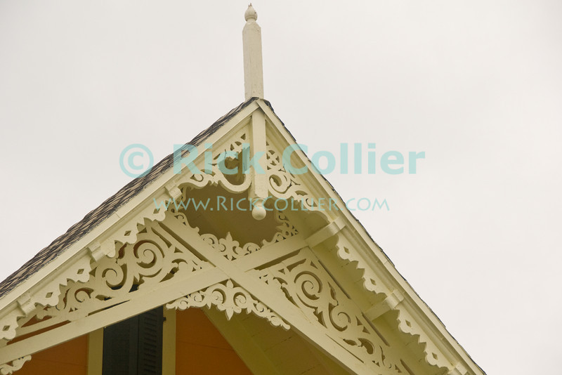 """""""Yellow eves"""" -- Ornate trimwork is common on the lovely beach houses at Ocean Grove, New Jersey, USA.<br /> <br /> <br /> USA """"New Jersey"""" NJ """"Ocean Grove"""" Ocean Grove building scrollwork trim detail onamentation decoration decor roof peak eve"""