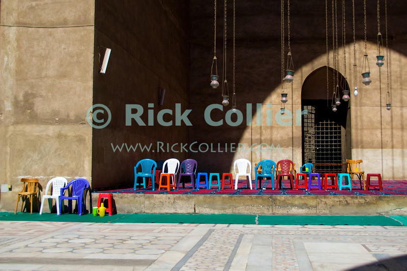 "Cairo, Egypt -- I was struck by the bright colors of these inexpensive and modern chairs, all neatly aligned in front of one of the iwans inside this historic site, the Sultan Hassan mosque.   © Rick Collier / RickCollier.com<br /> <br /> <br /> <br /> travel; vacation; tour; tourism; tourist; destination; Egypt; Cairo; mosque; madrassa; Sultan; Hassan; ""Sultan Hassan""; chairs; color; colorful; chair; plastic; lamp; lamps; iwan"