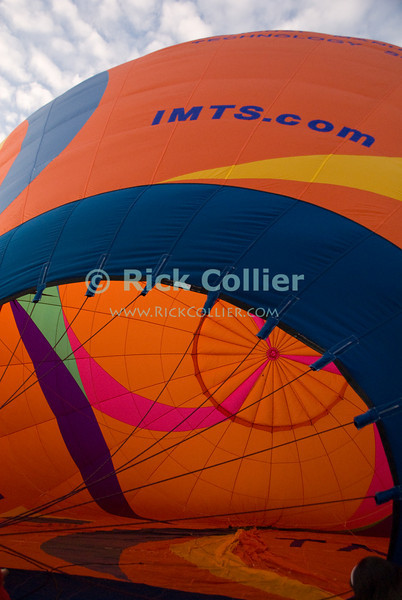 """The seams and fabric make a symetrical pattern in brightly colored fabric at the very top of a hot-air balloon, visible from inside as the bag inflates.  © RickCollier.com<br /> <br /> <br /> <br /> <br /> <br /> """"balloon festival""""; USA; Virginia; Winchester; """"Long Branch""""; """"Long Branch Farm""""; morning; balloon; lift; """"balloon lift""""; """"hot air balloon""""; fabric; seam; seams; pattern"""