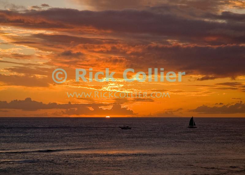 Waikiki, Honolulu, Oahu, Hawaii.  Sailboats return home in a feiry sunset.<br /> <br /> <br /> <br /> <br /> Hawaii Honolulu Waikiki sunset clouds sea view ocean view reflection sail boat sailboat boats