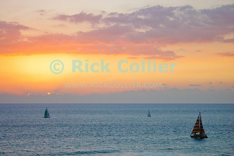 The orange sunset illuminates the clouds and reflects from the sea, backlighting boats off the reef and beach.  Waikiki, Honolulu, Oahu, Hawaii.  © Rick Collier<br /> <br /> <br /> <br /> <br /> <br /> <br /> <br /> Hawaii Hawai'i Oahu Honolulu Waikiki beach bay sail boats sailboat sailboats city skyline seashore evening sun set sunset