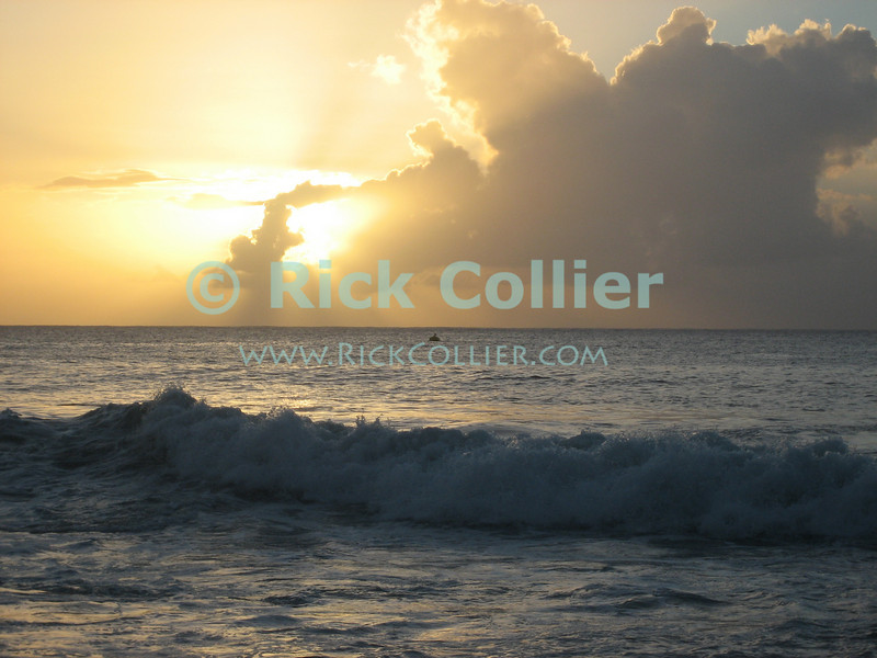 St. Eustatius (Statia) - The sun begins to disappear behind a rain storm at sea, viewed from a Caribbean beach at sunset. © Rick Collier