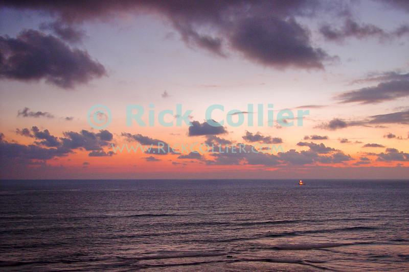 The sky fades to red as the sun sets over the ocean.  Waikiki, Honolulu, Oahu, Hawaii.  © Rick Collier<br /> <br /> <br /> <br /> <br /> <br /> <br /> <br /> Hawaii Hawai'i Oahu Honolulu Waikiki beach bay seashore evening sun set sunset