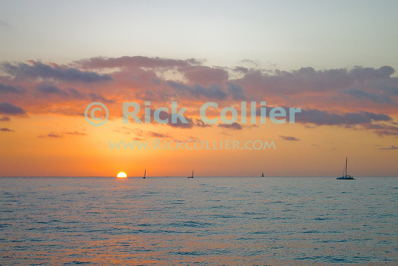 Sails are furled as the breeze dies when the sun goest down off Waikiki, Honolulu, Oahu, Hawaii.  © Rick Collier<br /> <br /> <br /> <br /> <br /> <br /> <br /> <br /> Hawaii Hawai'i Oahu Honolulu Waikiki sunset sun set sail sailboat sea ocean