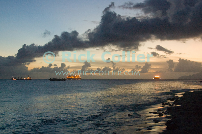 """A beautiful Caribbean sunset silhouettes the beach, with tankers beyond waiting at the oil terminal.  Saba is visible in the distance.  St. Eustatius (Statia), Netherlands Antilles.<br /> <br /> <br /> <br /> <br /> """"St. Eustatius"""" """"Saint Eustatius"""" Statia Netherlands Antilles """"Lesser Antilles"""" Caribbean Saba sunset beach ship tanker clouds sky ocean sea reflection running lights"""