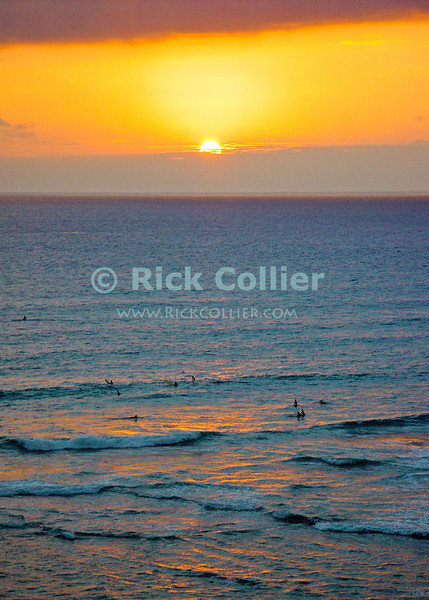 The orange sunset is reflected in the sea, backlighting swimmers off the reef and beach.  Waikiki, Honolulu, Oahu, Hawaii.  © Rick Collier<br /> <br /> <br /> <br /> <br /> <br /> <br /> <br /> Hawaii Hawai'i Oahu Honolulu Waikiki beach bay seashore evening sun set sunset swimmer surf surfer surfing