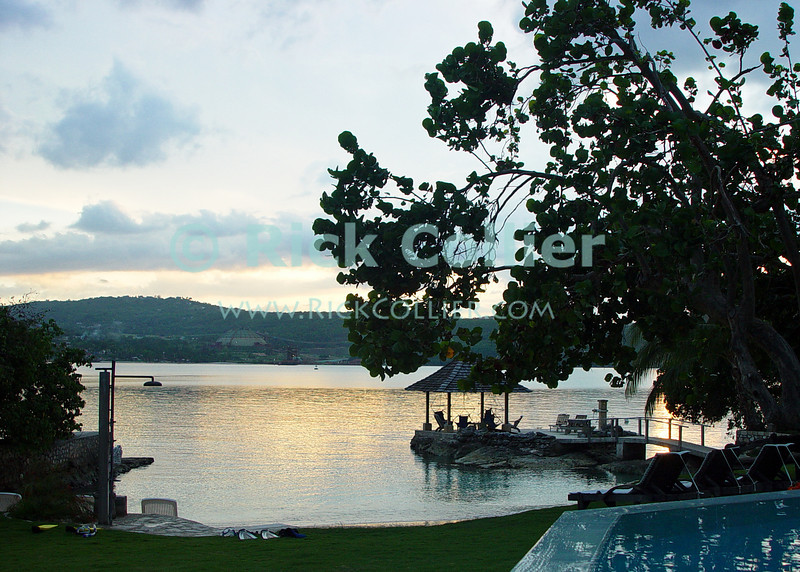 Amanoka Villa, Discovery Bay, Saint Ann Parish, Jamaica.  The yellow and orange sunset reflecting off the bay is framed by dissipating afternoon clouds, making a beautiful, serene sight from the infinity pool at Amanoka.  © Rick Collier<br /> <br /> <br /> <br /> <br /> <br /> Jamaica Discovery Bay Dry Harbor Bay Amanoka Villa tropical island paradise relaxation calm water inifinity pool bay ocean reflection sunset orange yellow clouds gazebo shadow backlight