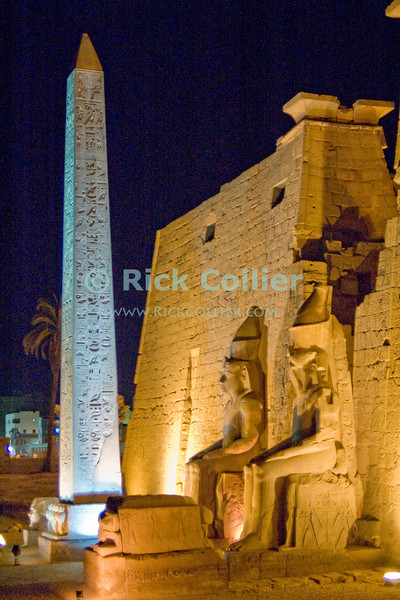 """The """"front"""" entrance to Luxor Temple, Egypt, is illuminated at night.  Dedicated to the Theban triad of Amun-Min, Mut, and Konsu, Luxor Temple stands in the center of town.  The statues are of Ramses II, to whom the first court in the temple is dedicated.  There were originally two obelisks here -- the second was removed and now stands at the Louvre in Paris.  Originally joined by a road to the Temple of Amon at Karnak, Luxor was temple was considered the """"harem of the south,"""" the home of Amon's wife Mut and son Khonsu.  Once a year, a ceremonial procession took the statue of Amon from Karnak to spend the night with his family at Luxor.  © Rick Collier<br /> <br /> <br /> <br /> <br /> <br /> <br /> Egypt Egyptian Karnak Luxor Amon Amun tourist tourism history historic antiquity antiquities ruins temple tomb pylon wall column pillar ramp ancient 'ancient Egypt' Thebes Theban Thebian Mut Konsu Amun-Min Khonsu obelisk pylon wall Ramses 'Ramses II' statue colossus colossi night illumination lights dark 'after dark' nighttime"""