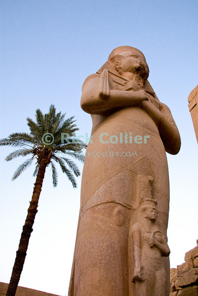 """Luxor, Egypt -- A statue of Pharoah Ramses III towers outside the temple to Ramses between the first and second pylons at Karnak Temple.  The small figure in front of the pharoah would be his wife.  Karnak was built over many generations of Egyptian pharoah, as each successive king added pieces to this temple honoring the most significant god of the ancient Egyptian pantheon, the god Amun (later, Amon-Ra), the sun god. © Rick Collier / RickCollier.com.<br /> <br /> <br /> <br /> <br /> <br /> travel; vacation; tour; tourism; tourist; destination; Egypt; Luxor; Karnak; """"Karnak Temple""""; Amun; Amon; Amon-Ra; temple; hieroglyph; hieroglyphic; """"ancient Egypt""""; archeology; archeological; ruin; pylon; wall; pillar; statue; figure; Ramses; """"Ramses III"""""""