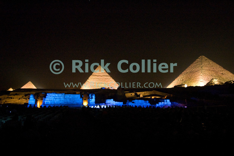 The three most famous pyramids at Giza, outside of Cairo Egypt, are all illuminated in the weekly presentation of the sound and light show.  The ruins in foreground are the remains of the valley temples that would have been the first stop in funerals of the kings and queens interred in the pyramids. © Rick Collier<br /> <br /> <br /> <br /> <br /> <br /> <br /> Egypt Egyptian Cairo Giza pyramid pyramids Sphinx Cheops 'Great Pyramid' 'Great Pyramid of Cheops' Chephren 'Pyramid of Chephren' Mycerinus 'Pyramid of Mycerinus' queen queens 'Queen's Pyramids' 'Queens Pyramids' night evening 'after dark' sound light 'sound and light' show presentation tourist tourism history historic antiquities 'ancient Egypt' ancient antiquity audience tomb tombs lights