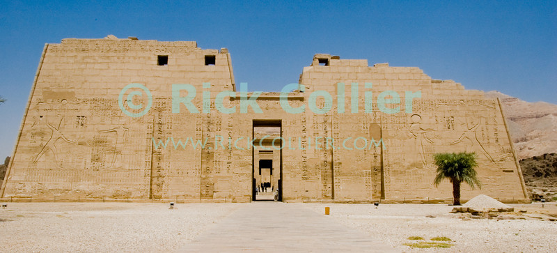 Medinet Habu -- the Mortuary Temple of Ramses III, near Luxor, Egypt.  The front wall (first pylon) of the temple looms large as the visitor approaches.  The wall is inscribed with important scenes from the pharoah's life, including scenes of taking and smiting prisoners.  © Rick Collier<br /> <br /> <br /> <br /> <br /> <br /> <br /> Egypt Egyptian Habu 'Medinet Habu' Luxor tourist tourism history historic antiquity antiquities Thebes Theban Thebian Nile 'Nile River' temple tomb monument souvenir shop town village 'Valley of the Kings' necropolis Ramses 'Ramses III'