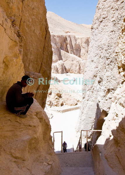 """Luxor, Egypt -- View of the """"Valley of the Dead"""" or """"Valley of the Kings"""" from the tomb of Thutmos III (Thutmes or Thutmosis III).  The valley is a canyon in the western wall of the Nile River valley, not far from Luxor.  To accomodate tourists, paths have been made with bordering walls and some stairs and railings installed.  Many of the more remote tombs have attendants and locals who guard the tombs and may also """"rent"""" pieces of cardboard for use as a fan in the humid caves or sell cool drinks.   © Rick Collier / RickCollier.com.<br /> <br /> <br /> <br /> <br /> <br /> travel; vacation; tour; tourism; tourist; destination; Egypt; Luxor; valley; """"Valley of the Dead""""; """"Valley of the Kings""""; kings; pharoah; pharoahs; tomb; temple; """"ancient Egypt""""; tombs; excavation; excavations; archaeology"""