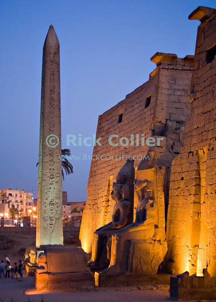 """Luxor, Egypt -- Statues and one remaining obelisk stand before the entrance (outer pylon) at Luxor Temple.  (The """"missing"""" obelisk, companion to the one remaining, now stands in Paris, France.)  Luxor temple was built principally by two pharoahs, Ramses II and Amenhotep III, and was the companion temple to Karnak for worship of the Theban triad of gods, Amun, his wife Mut, and their son Khonsu. While Karnak was the home of Amun, his wife Mut and son Khonsu resided at Luxor.  The two temples were linked by a road lined with sphinxes, the end of which is now visible at the approach to Luxor Temple © Rick Collier / RickCollier.com.<br /> <br /> <br /> <br /> <br /> <br /> travel; vacation; tour; tourism; tourist; destination; Egypt; Luxor; temple; hieroglyph; hieroglyphic; """"ancient Egypt""""; archeology; archeological; ruin; sphinx; """"Luxor Temple""""; Amenhotep; """"Ramses II""""; obelisk; Mut; Khonsu;"""