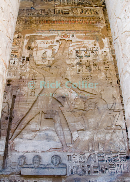 Medinet Habu -- the Mortuary Temple of Ramses III, near Luxor, Egypt.  The walls inside the temple's first and second courts are inscribed with important scenes from the pharoah's life.  This scene shows the pharoah smiting three prisoners, and displays evidence that he took their heads in battle.  The original paint and coloration have been protected by the extraordinary depth of the carvings and is still visible in some parts of the wall.  © Rick Collier<br /> <br /> <br /> <br /> <br /> <br /> <br /> Egypt Egyptian Habu 'Medinet Habu' Luxor tourist tourism history historic antiquity antiquities Thebes Theban Thebian Nile 'Nile River' temple tomb monument souvenir shop town village 'Valley of the Kings' necropolis Ramses 'Ramses III' smiting heiroglyph heiroglyphic