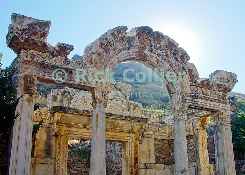 Temple of Hadrian, at Ephesus, in modern-day Turkey.  The Temple of Hadrian stands beside the main street.  Remaining carvings display scenes from Roman and Greek history.  The home of the Biblical Ephesians and site where portions of the Book may have been written, the city dates from the Hellenestic (Greek) empire and was subsequently one of the principle cities of the Roman empire.  The city was famed for the Temple of Artemis (Diana), who had her chief shrine there, the Library of Celsus, and its theater, which was capable of holding 25,000 spectators. Ephesus is believed to be the city of the Seven Sleepers. The story of the Seven Sleepers, considered saints by Christians and Muslims, tells that they were persecuted because of their belief in God and that they slept in a cave near Ephesus for centuries.  © Rick Collier<br /> <br /> <br /> <br /> <br /> <br /> <br /> Turkey Ephesus Ephessus Rome Roman Empire Greek Greece Hellenistic Artemis Diana Cayster River Bible Biblical ruin ruins archeology archeological tour tourims tourist view street road column columns temple temples theater amphitheater library Hadrian 'Temple of Hadrian' 'Hadrian's Temple'