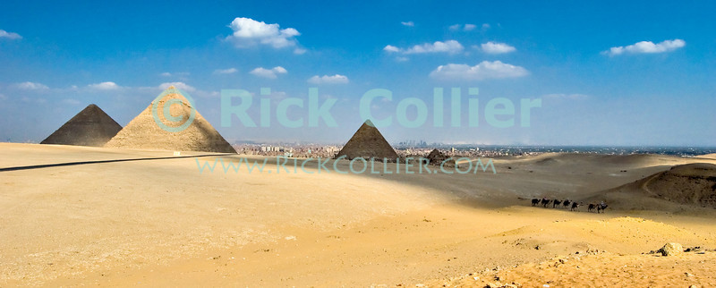 """Giza, Cairo, Egypt -- Locals lead tourists on camel rides near the pyramids at Giza, with the city of Cairo sprawled in the background. © Rick Collier / RickCollier.com<br /> <br /> <br /> <br /> <br /> <br /> travel; vacation; destination; Egypt; Cairo; Giza; pyramids; pyramid; """"Pyramids at Giza""""; tourist; tourism; camel; ride; """"camel ride""""; """"camel caravan""""; desert; panorama; view; Cheops; Khufu; Khafre; Kephren; Menkaure; Mykerinus; """"queen's pyramids"""""""