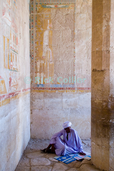 """Luxor, Egypt -- A local rests in the shade under a mural of protection.  Note that under the goddess of protection Nekhbet (the vulture), half of the hieroglyphic mural showing the monarch / pharoah has been destroyed -- probably to eliminate Hatshepsut from the God's favor. © Rick Collier / RickCollier.com.<br /> <br /> <br /> <br /> <br /> <br /> travel; vacation; tour; tourism; tourist; destination; Egypt; Luxor; valley; """"Valley of the Dead""""; """"Valley of the Kings""""; kings; pharoah; pharoahs; tomb; temple; """"ancient Egypt""""; tombs; excavation; excavations; archaeology; Hatshepsut; """"Hatshepsut Temple""""; """"Deir el-Bahri""""; """"Dar el-Bahri""""; engraving; hieroglyphs; hieroglyphics; art; wall; """"wall art"""";"""