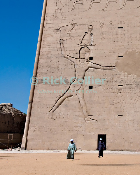 "Edfu, Egypt -- Local workmen emerge from a door in the outer pylon of the ancient Egyptian temple at Edfu.  Edfu temple is relatively new by Egyptian standards, having been built during the Ptolemaic dynasties in the period 237 to 57 BC.  Because it was built by the last Egyptian pharonic dynasties, it was not canibalized by successor dynasties and so is well preserved.  Edfu Temple is dedicated to the Falcon god Horus. © Rick Collier / RickCollier.com.<br /> <br /> <br /> <br /> travel; vacation; tour; tourism; tourist; destination; Egypt; Edfu; ""Edfu Temple""; Horus; Ptolemaic; temple; pylon; falcon; ""falcon god""; hieroglyph; hieroglyphic; ""ancient Egypt""; Ptolemy; wall; column; art; ancient; antiquity; antiquities;"