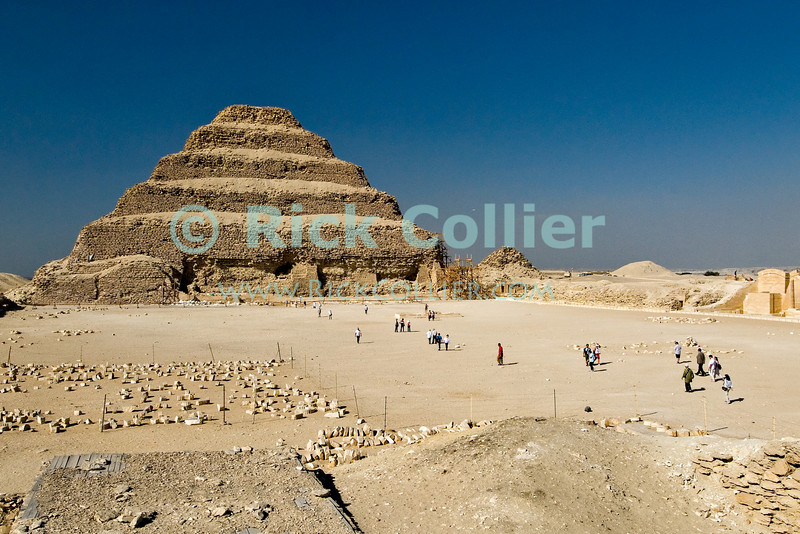 "Saqqara, Cairo, Egypt -- Part of what was once a magnificant complex, the famous step pyramid of Djoser (Dozer) stands before a large courtyard arena and surrounded by the remains of the many buildings that originally bounded its precincts. © Rick Collier / RickCollier.com.<br /> <br /> <br /> <br /> <br /> <br /> travel; vacation; tour; tourism; tourist; destination; Egypt; Cairo; Saqqara; Djoser; Dozer; pyramid; ""step pyramid"";"
