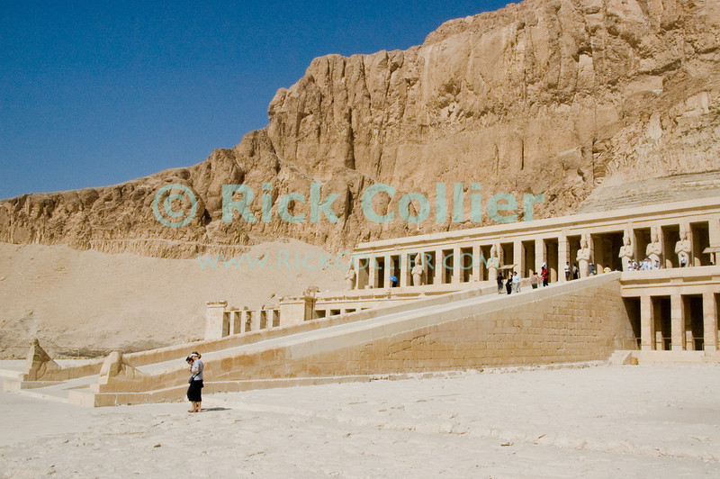 Deir el-Bahri (Temple of Hatshepsut), near Luxor, Egypt.  The Temple built as her tomb by Hatshepsut, the only woman to rule ancient Egypt as a man (pharoah), is built high into the cliff walls on the opposite side of the mountain from the Valley of the Kings.  Hatshepsut was scourged by her successors, as the only woman who ever had the temerity to rule Egypt as a man (pharoah).  As a woman, she could not be burried in the valley of the kings, but legend says this temple represents her way of getting around that rule -- by placing her tomb down a deep tunnel behind this temple, with the burial chamber beyond the half-way point, in the side of the mountain that faces the all-male Valley of the Kings.  © Rick Collier<br /> <br /> <br /> <br /> <br /> <br /> <br /> Egypt Egyptian Karnak Luxor tourist tourism history historic antiquity antiquities Thebes Theban Thebian Nile 'Nile River' temple tomb monument Hatshepsut pharoah 'Deir el-Bahri'
