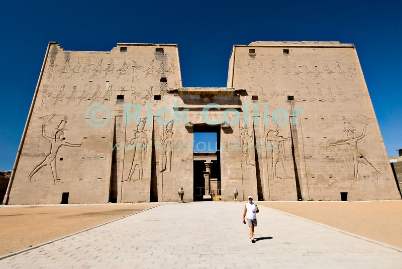 """Edfu, Egypt -- The impressive outer wall (pylon) at Edfu Temple.  Edfu temple is relatively new by Egyptian standards, having been built during the Ptolemaic dynasties in the period 237 to 57 BC.  Because it was built by the last Egyptian pharonic dynasties, it was not canibalized by successor dynasties and so is well preserved.  Edfu Temple is dedicated to the Falcon god Horus. © Rick Collier / RickCollier.com.<br /> <br /> <br /> <br /> travel; vacation; tour; tourism; tourist; destination; Egypt; Edfu; """"Edfu Temple""""; Horus; Ptolemaic; temple; pylon; falcon; """"falcon god""""; hieroglyph; hieroglyphic; """"ancient Egypt""""; Ptolemy; wall; column; art; ancient; antiquity; antiquities;"""