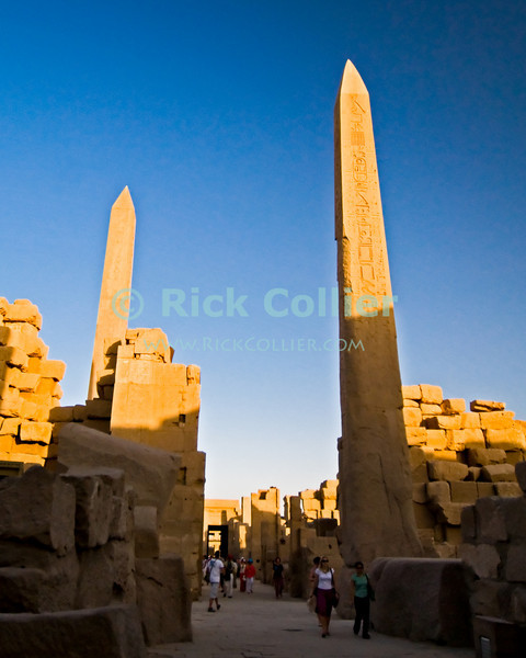 """Luxor, Egypt -- Queen (pharoah) Hatshepsut had two massive obelisks erected near the main temple of Amun at Karnak.  Subsequent pharoahs sought to remove her influence but could not deface stellae honoring Amun, so they built walls to hide the obelisks from view and worship.  Karnak was built over many generations of Egyptian pharoah, as each successive king added pieces to this temple honoring the most significant god of the ancient Egyptian pantheon, the god Amun (later, Amon-Ra), the sun god. © Rick Collier / RickCollier.com.<br /> <br /> <br /> <br /> <br /> <br /> travel; vacation; tour; tourism; tourist; destination; Egypt; Luxor; Karnak; """"Karnak Temple""""; Amun; Amon; Amon-Ra; temple; hieroglyph; hieroglyphic; """"ancient Egypt""""; archeology; archeological; ruin; pylon; wall; column; pillar; obelisk"""